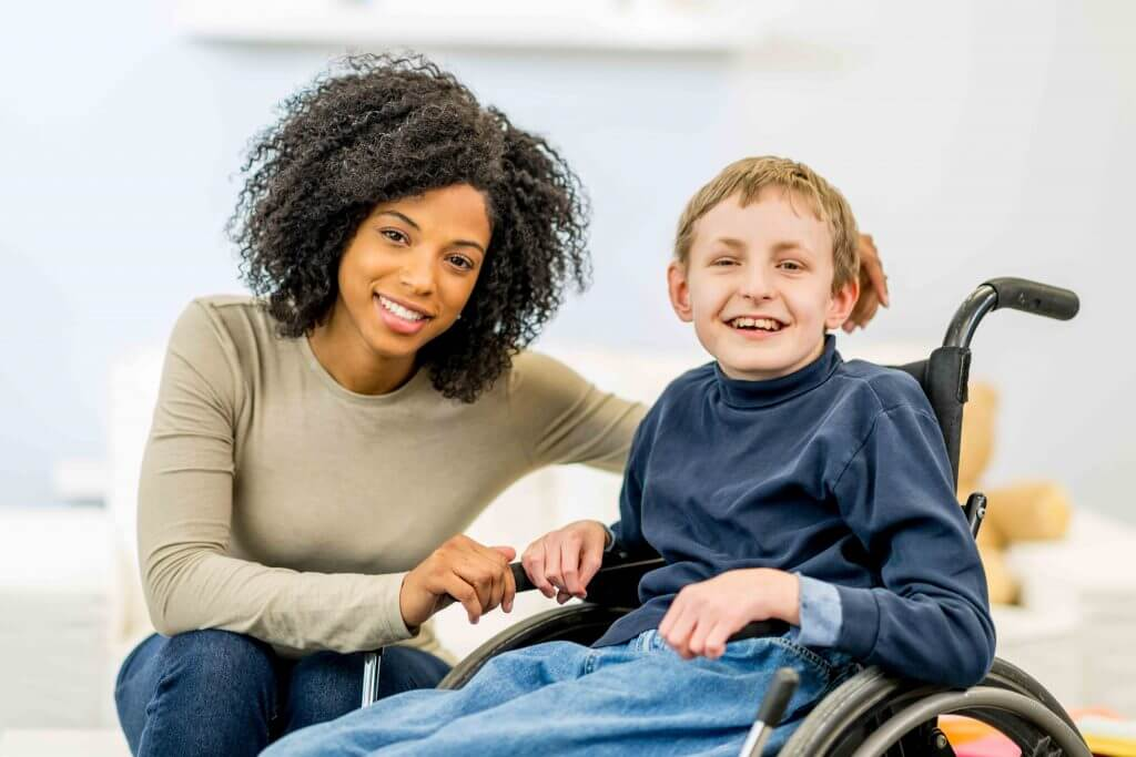 A manos special care helper kneeling by a young boy in a wheelchair