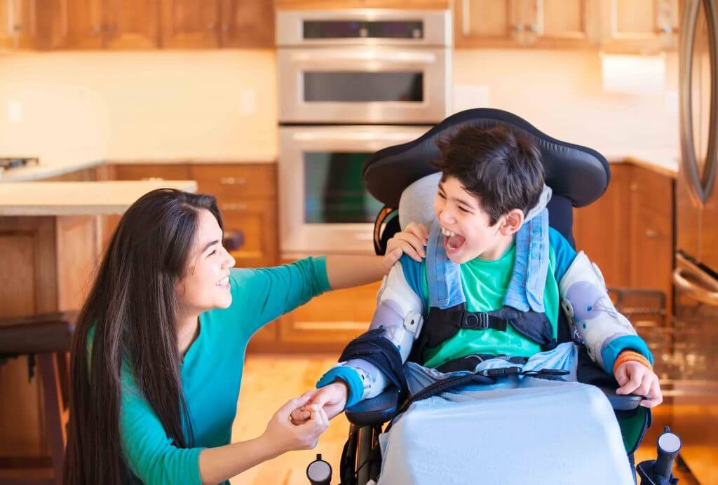 A slider image of a mother smiling with her special needs child inside their home