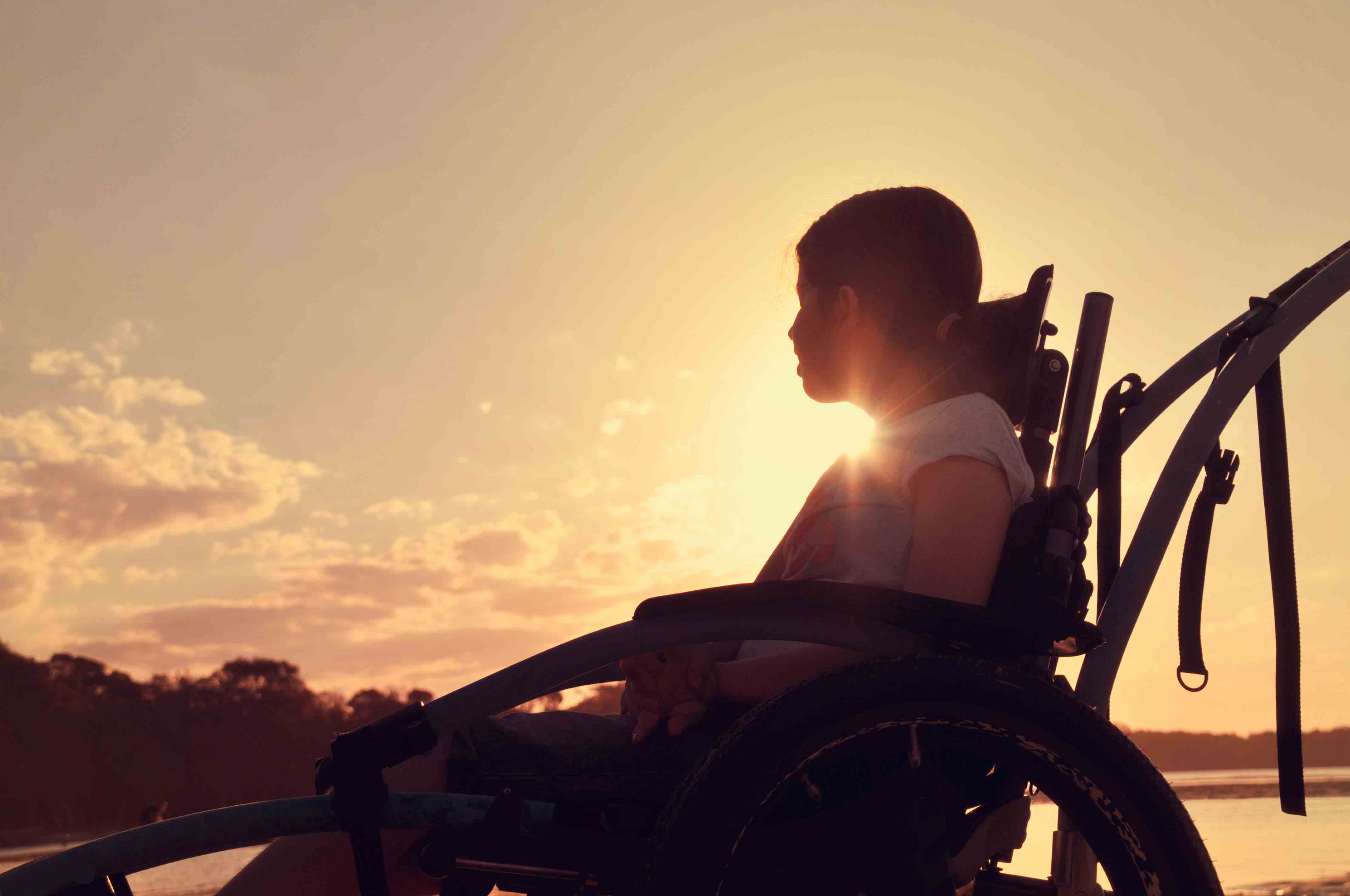 girl in a wheelchair looking out to a lake at sunset